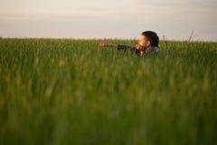 El adolescente miente en la hierba alta en la puesta del sol Fotografía de archivo