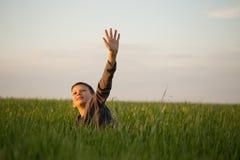 El adolescente miente en la hierba alta en la puesta del sol Foto de archivo libre de regalías