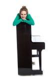 El adolescente miente en piano en camisa verde Imagenes de archivo