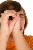 El adolescente mira a través de las manos Foto de archivo libre de regalías
