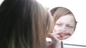El adolescente modelo de la belleza que mira en el espejo y que comprueba su piel, aplicándose compone 4K almacen de video