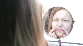 El adolescente modelo de la belleza que mira en el espejo y que comprueba su piel, aplicándose compone 4K almacen de metraje de vídeo