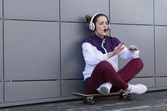 El adolescente moderno de la muchacha canta una canción en los auriculares con el monopatín Imágenes de archivo libres de regalías