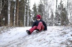El adolescente monta de una colina en la madera nevada. Fotografía de archivo libre de regalías