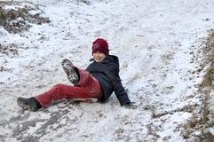 El adolescente monta de una colina en la madera nevada. Foto de archivo