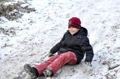 El adolescente monta de una colina en la madera nevada. Fotos de archivo libres de regalías