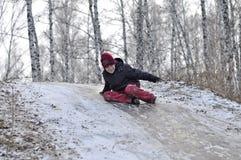 El adolescente monta de una colina en la madera nevada. Fotos de archivo