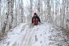 El adolescente monta de una colina en la madera nevada. Imagenes de archivo
