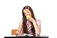 El adolescente muerde en la manzana en escuela Imagen de archivo
