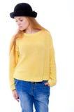 El adolescente o la mujer joven en suéter amarillo y sombrero negro mira Fotografía de archivo libre de regalías