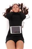 El adolescente observa la mentira cerrada en el piso con PC de la tableta y h Foto de archivo libre de regalías