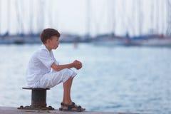 El adolescente pensativo mira la nave el mar y los sueños Fotografía de archivo