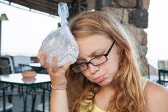 El adolescente pone el hielo en una bolsa de plástico a la cabeza Fotografía de archivo