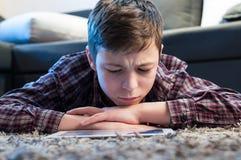 El adolescente pone en el piso en el cuarto Fotos de archivo