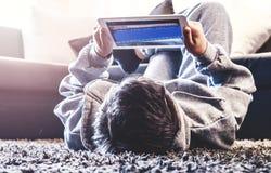 El adolescente pone en el piso en el cuarto Foto de archivo