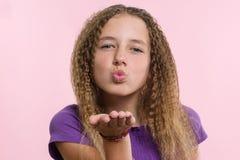 El adolescente positivo atractivo del retrato envía beso del aire sobre fondo rosado Imagen de archivo libre de regalías