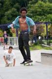 El adolescente practica el andar en monopatín en el parque del monopatín Foto de archivo libre de regalías