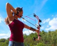 El adolescente practica el tiro al arco en un caliente, día de verano foto de archivo