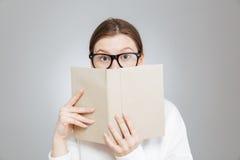 El adolescente preguntado en vidrios cubrió la cara con el libro Fotografía de archivo