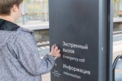 El adolescente presiona el botón de la llamada de emergencia en la estación Imagen de archivo