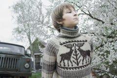 El adolescente que anticipa en suéter lanoso de los ciervos del vintage al aire libre en fruta floreciente cultiva un huerto en l Foto de archivo