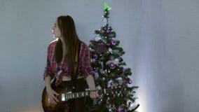El adolescente que juega la canción de la guitarra, del canto y baile cerca del árbol de navidad almacen de video