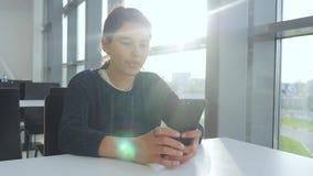 El adolescente que la muchacha está charlando comunica en el mensajero en un smartphone en un café en una luz del sol de la tabla metrajes