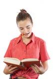 El adolescente que lee un libro con el lápiz en aquí articula, aislado Imagen de archivo libre de regalías