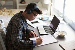 El adolescente que lleva los auriculares trabaja en el escritorio en su dormitorio Foto de archivo