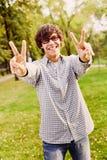 El adolescente que muestra la victoria firma adentro el parque Foto de archivo