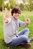 El adolescente que muestra la victoria firma adentro el parque Fotografía de archivo libre de regalías