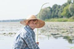 El adolescente que pesca con caña con la caña de pescar verde hecha a mano de la ramita está mirando detrás Imagenes de archivo