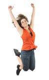 El adolescente que salta con la camisa anaranjada en el fondo blanco Imágenes de archivo libres de regalías