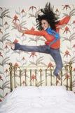 El adolescente que salta en cama Imágenes de archivo libres de regalías
