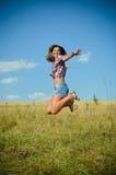 El adolescente que salta en campo del verano Imagen de archivo