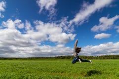 el adolescente que salta en campo del verano, Imágenes de archivo libres de regalías
