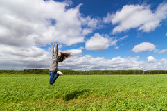 el adolescente que salta en campo del verano, Fotos de archivo libres de regalías