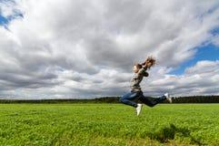 el adolescente que salta en campo del verano, Imagen de archivo