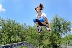 El adolescente que salta en el aire en rollerblades Fotos de archivo libres de regalías