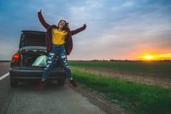 El adolescente que salta en el camino abierto cerca del coche imagenes de archivo