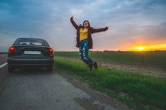 El adolescente que salta en el camino abierto cerca del coche Imagen de archivo libre de regalías