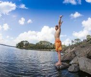 El adolescente que salta en el río Fotografía de archivo