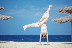 El adolescente que salta en la playa Imagen de archivo