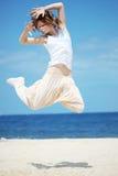 El adolescente que salta en la playa Imagenes de archivo