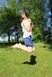 El adolescente que salta en prado Fotografía de archivo