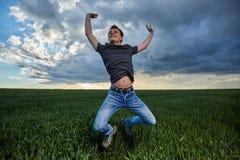 El adolescente que salta para la alegría al aire libre Fotos de archivo