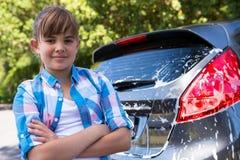 El adolescente que se colocaba con los brazos cruzó cerca de un coche Foto de archivo libre de regalías