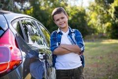 El adolescente que se colocaba con los brazos cruzó cerca de un coche Imagenes de archivo