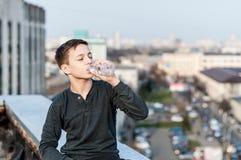 El adolescente que se sienta en el borde del tejado bebe el agua Imagen de archivo libre de regalías