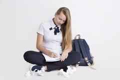 El adolescente que se sienta en piso escribe la pluma en el papel Foto de archivo